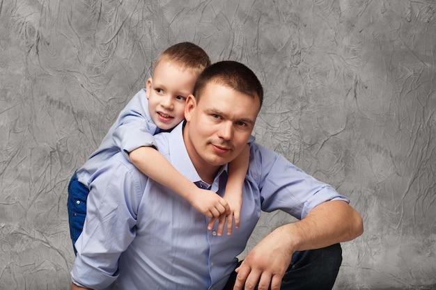 Ojciec i synek w niebieskich koszulach przed szarą teksturą