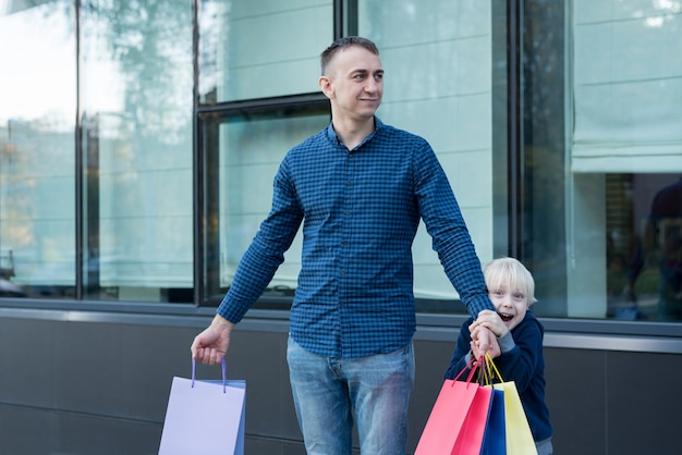 Ojciec i synek z kolorowe torby na zakupy na ulicy.