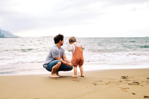 Ojciec i trzyletni syn cieszą się pochmurnym popołudniem na plaży w weekend