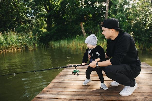 Ojciec i uroczy roczny syn łowiący wędkę w naturze. koncepcja ucieczki na wsi. artykuł o dniu połowów.