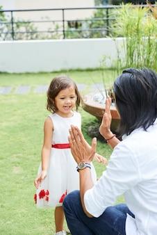 Ojciec i wesoła córeczka klaszczą w dłonie podczas zabawy na podwórku