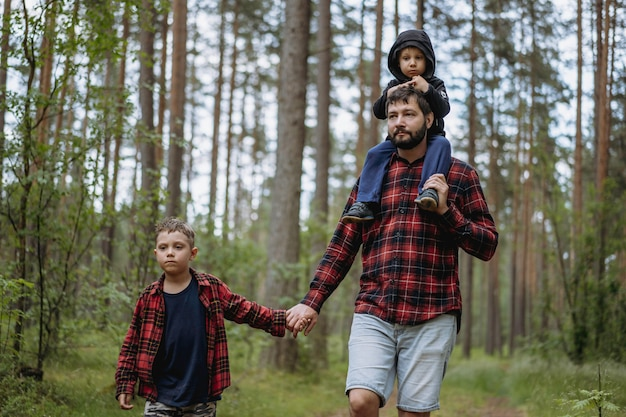 Ojciec idzie drogą w lesie z dwoma synami