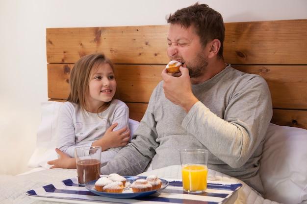 Ojciec jedzenia cupcake obok jego córki