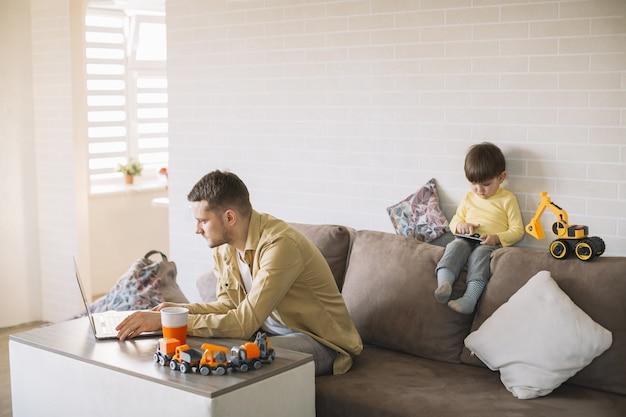 Ojciec jedzenia i pracy z domu długi widok
