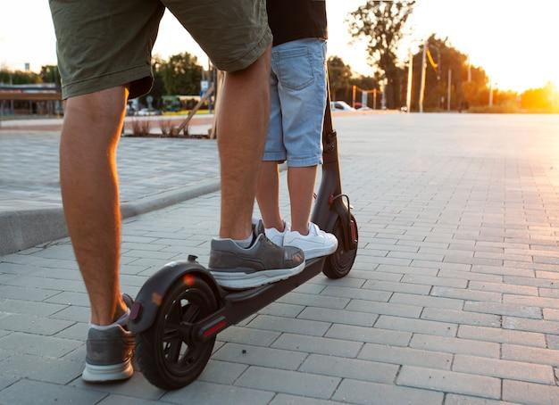 Ojciec jedzie z synem elektryczną hulajnogą po pustym parkingu