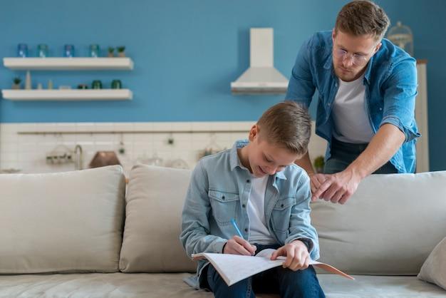 Ojciec jest pomocny w odrabianiu lekcji przez syna