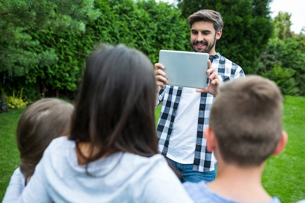 Ojciec klikając obraz rodziny z cyfrowego tabletu w parku
