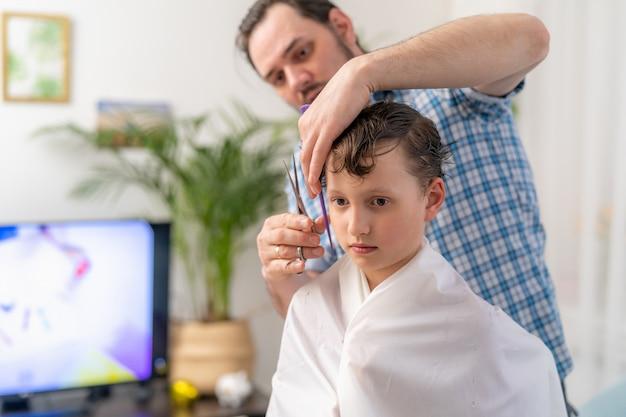 Ojciec kosi syna w domu. potrzeba aktualizacji włosów dziecka
