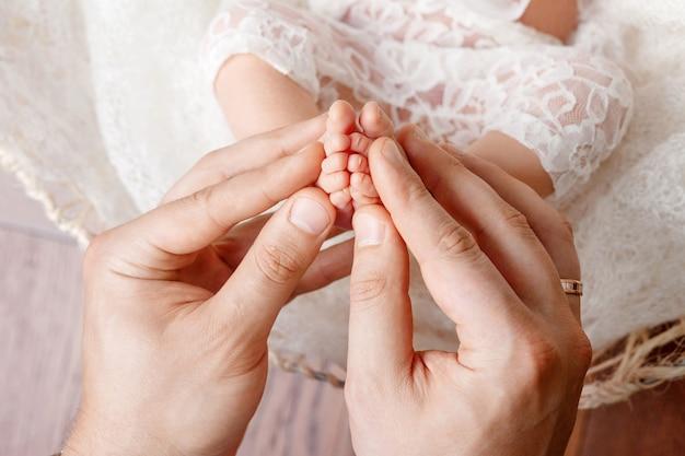 Ojciec lub lekarz masujący stopę małego dziecka. ojciec delikatnie trzymając w rękach nogi noworodka. szczęśliwa rodzina .