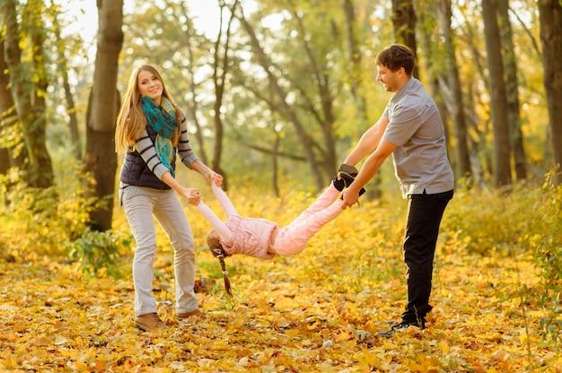Ojciec mama i ich córka bawią się razem. rodzice trzymają ręce i nogi córki i radośnie ją podnoszą.