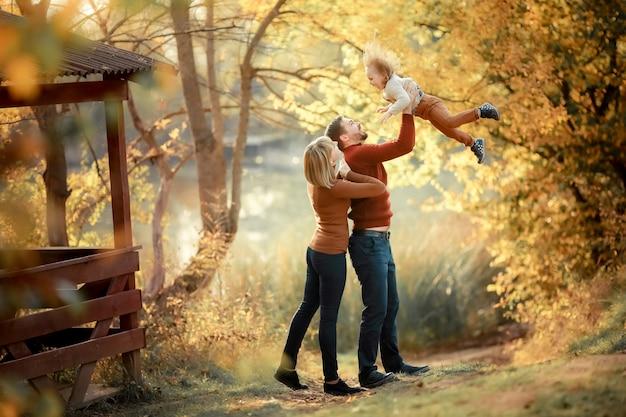Ojciec matka i córeczka w ramionach rodziców na leśnej ścieżce między wysokimi żółtymi drzewami