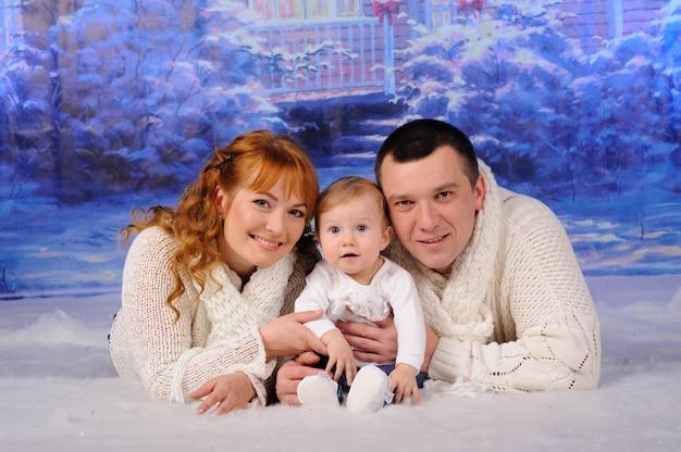 Ojciec, matka i córka leżą na śniegu.