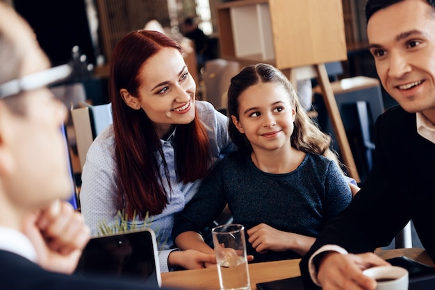 Ojciec, matka i córka siedzą w biurze prawnika.