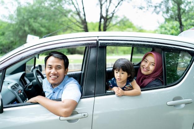 Ojciec, matka i córka wyglądają przez otwarte okna