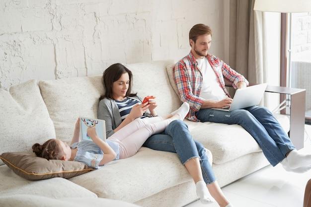 Ojciec, matka i córka za pomocą urządzeń elektronicznych, siedząc na kanapie w salonie.
