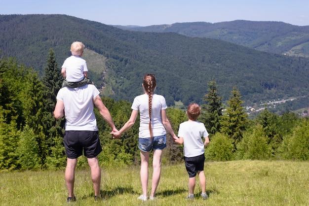 Ojciec, matka i dwaj mali synowie stoją na zielonym polu zalesionych wzgórz. wartości rodzinne