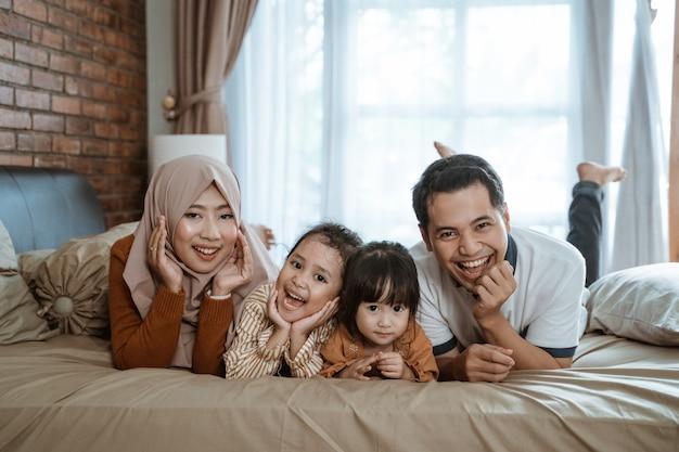 Ojciec, matka i dwie córki śmieją się radośnie, leżąc na łóżku