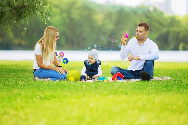 Ojciec, matka i młody syn na pikniku w parku.