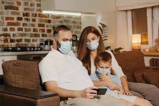 Ojciec, matka i syn siedzą na kanapie w medycznych maskach na twarz, aby uniknąć rozprzestrzeniania się koronawirusa (covid-19). rodzina podczas kwarantanny w domu. krewni cieszą się treścią na smartfonie