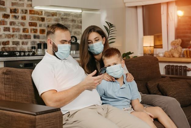 Ojciec, matka i syn siedzą na kanapie w medycznych maskach na twarz, aby uniknąć rozprzestrzeniania się koronawirusa (covid-19). rodzina podczas kwarantanny w domu. krewni czytają wiadomości na smartfonie na kanapie