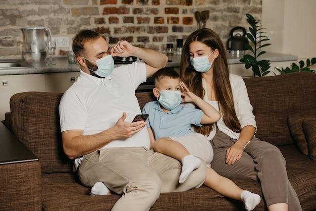 Ojciec, matka i syn siedzą na kanapie w medycznych maskach na twarz, aby uniknąć rozprzestrzeniania się koronawirusa (covid-19). rodzina podczas kwarantanny w domu. tata i dziecko sprawdzają swoje maski.