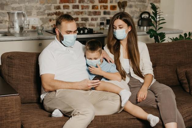 Ojciec, matka i syn siedzą na kanapie w medycznych maskach na twarz, aby uniknąć rozprzestrzeniania się koronawirusa (covid-19). rodzina podczas kwarantanny w domu. tata pokazuje wiadomości swoim krewnym