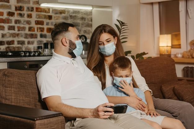 Ojciec, matka i syn siedzą na kanapie w medycznych maskach na twarz, aby uniknąć rozprzestrzeniania się koronawirusa (covid-19). rodzina podczas kwarantanny w domu. tata pokazuje wideo swoim bliskim