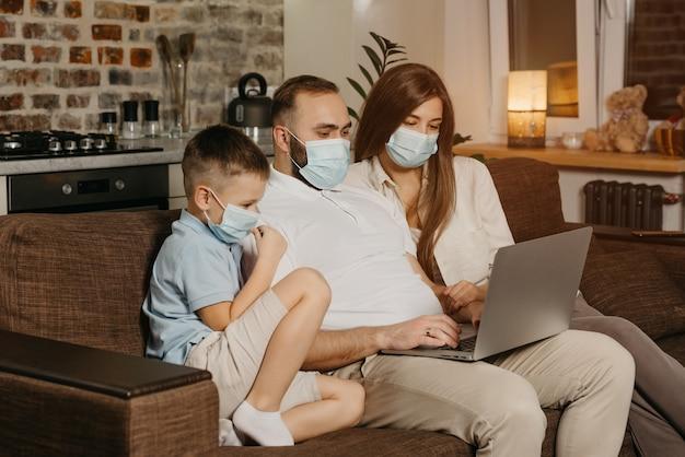 Ojciec, matka i syn siedzą na sofie w maskach na twarz, aby uniknąć rozprzestrzeniania się koronawirusa (covid-19).