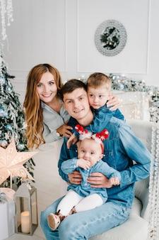Ojciec, matka trzyma synka i córkę w pobliżu choinki