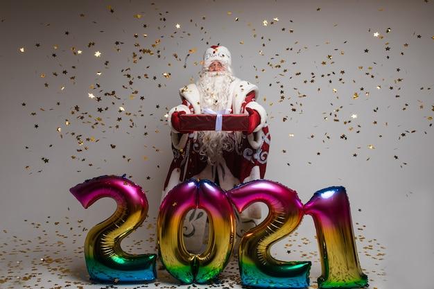 Ojciec mróz z balonami z numerami 2021 z prezentem, na białym tle na białej ścianie