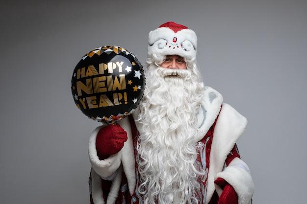 Ojciec mróz z długą brodą trzyma czarny balon, zdjęcie na szarej ścianie
