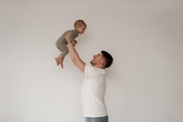 Ojciec na urlopie macierzyńskim na tle białej ściany bawi się z dzieckiem, podnosząc blat, trzymając go na wyciągnięcie ręki, oboje uśmiechnięci.