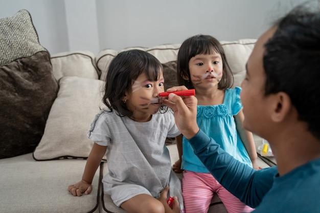 Ojciec namaluj dwie córki na twarzy
