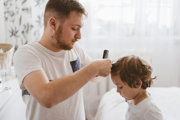 Ojciec obcina włosy jej syna w pokoju. rodzina podczas kwarantanny