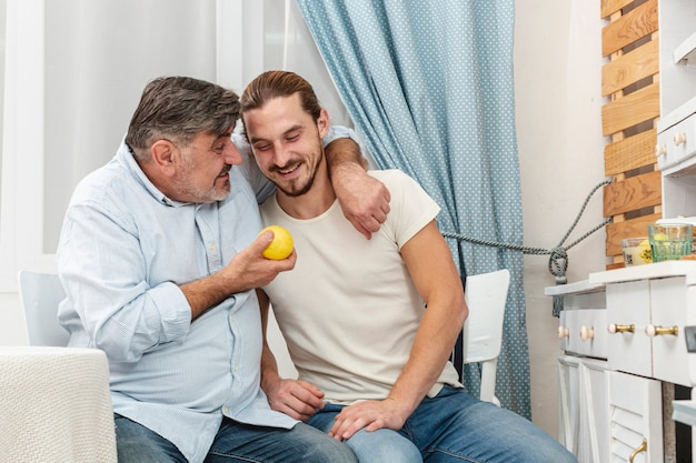 Ojciec obejmuje syna i trzyma smakowitego jabłka