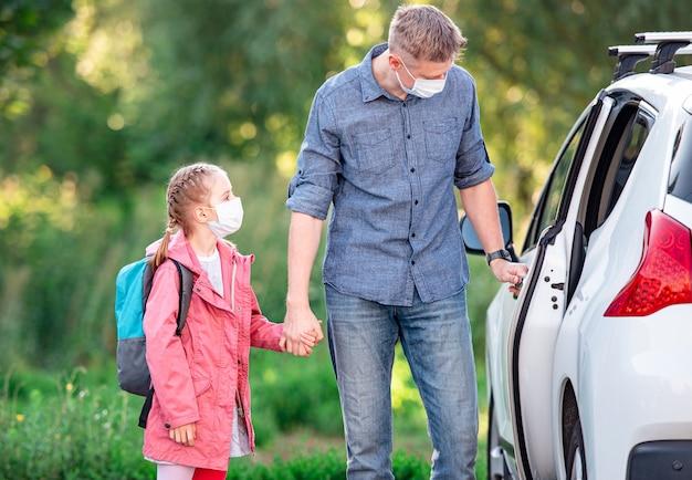 Ojciec odwozi córkę do szkoły podczas pandemii koronawirusa
