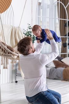 Ojciec podnoszący swoje małe niemowlę w powietrzu bawiące się w domu