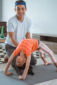 Ojciec pomaga córce rozciągać w domu. dziecko ćwiczy z rodzicem robi gimnastyczne