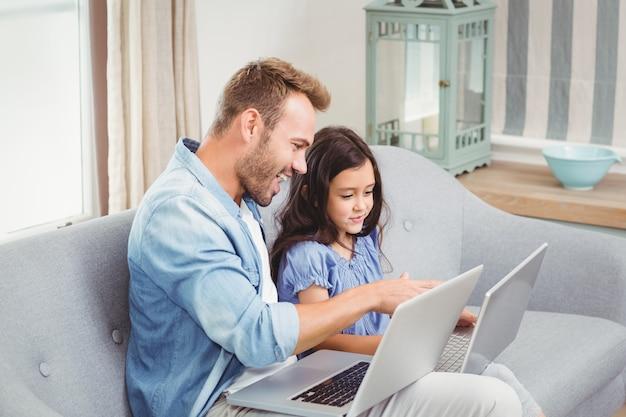 Ojciec pomaga córki w użyciu laptopa
