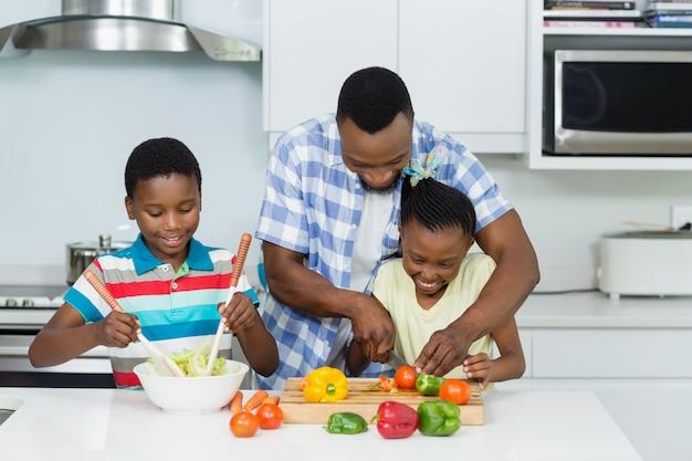 Ojciec pomaga dzieciom w przygotowaniu sałatki w kuchni