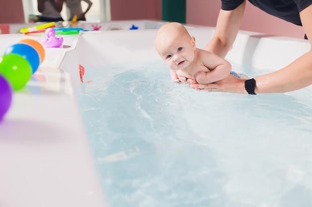 Ojciec pomaga dziecku podczas lekcji pływania w basenie.
