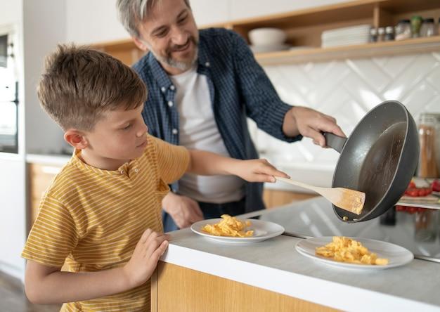 Ojciec pomaga dziecku w średnim ujęciu