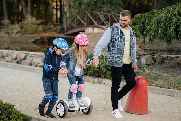 Ojciec pomaga i uczy swoje małe dzieci jeździć na segwayu w parku podczas zachodu słońca.
