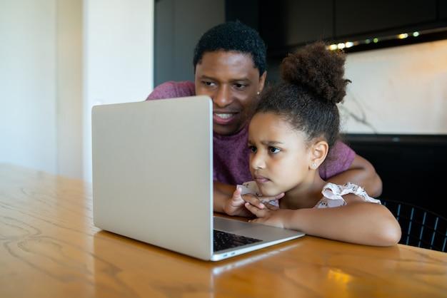 Ojciec pomaga i wspiera swoją córkę w szkole online podczas pobytu w domu