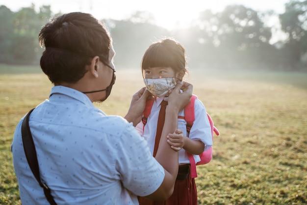 Ojciec pomaga jej córce założyć maskę przed pójściem do szkoły