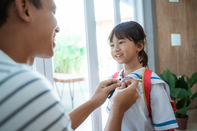 Ojciec pomaga jej maluchowi przygotować się do szkoły rano