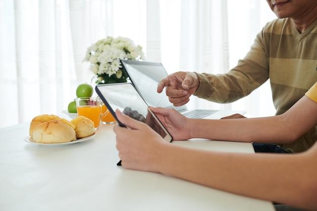 Ojciec pomaga nastoletniemu synowi zainstalować aplikację do nauki online na tablecie, gdy siedzą przy stole w kuchni