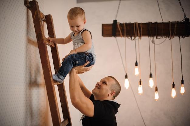 Ojciec pomaga swojemu małemu synowi wspinając się po drabinie