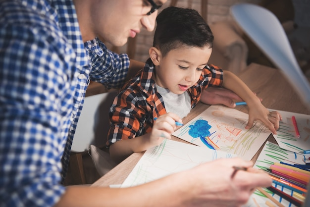 Ojciec pomaga synowi rysować na papierze w nocy w domu.