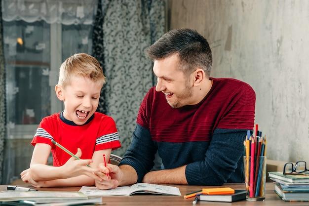 Ojciec pomaga synowi w odrabianiu lekcji w szkole.